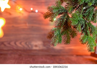 Christmas background. Spruce branch on a wooden background. Garland in the background. Focus on the branch.