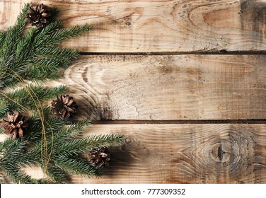 Christmas background with spruce branches and cones on a rough wooden background - top view