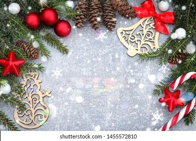 Christmas background. Spruce branches, fir cones and festive decor on a gray background. Place for text. Greeting card.