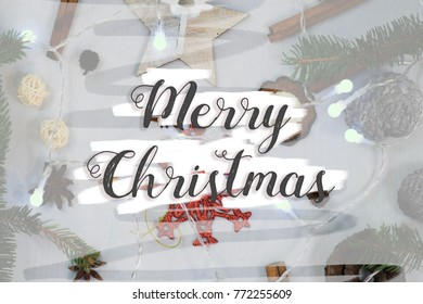 Christmas background with spruce springs and holiday decorations. Christmas tree lights. Merry Christmas text