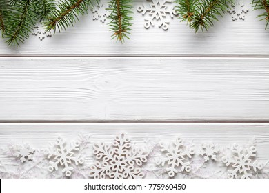Christmas background - spruce tree and snowflakes on white wooden table