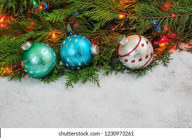 Christmas background with teal blue, red and silver ornaments, colorful string of lights and green Christmas tree garland border in snow; holiday background with white copy space