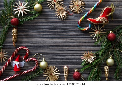 Christmas background (template) with new year balls, handmade straw ornaments, spruce branches and sweets on a dark wooden textured surface. View from above.