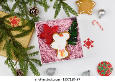 Christmas Background. Top View Of Christmas Boxe with lollipops and mouse shaped gingerbread and christmas tree branches and decorations on blue background. xmas and new year card top view flat lay