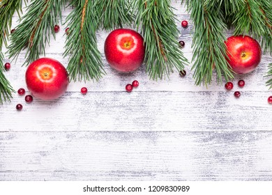 Christmas background with tree branches, red apples and cranberries. Light wooden table. Top view. Copy space