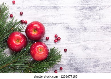Christmas background with tree branches, red apples and cranberries. Light wooden table. Snowfall drawing effect. Top view. Copy space