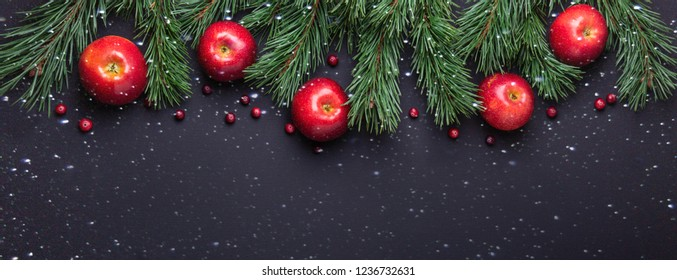 Christmas background with tree branches, red apples and cranberries. Dark wooden table. Snowfall drawing effect. Top view. Copy space
