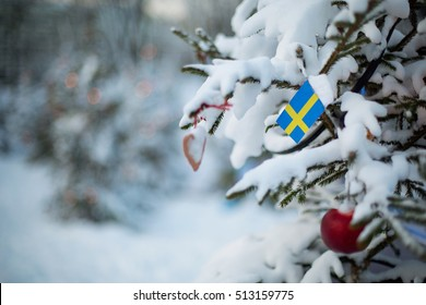 Christmas background. Christmas tree covered with snow and decorations and a flag of Sweden. Swedish flag closeup. Winter scene outdoor. Sverige