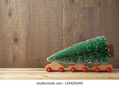 Christmas background with tree on toy car on wooden table