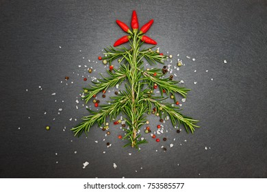 Christmas background with Christmas tree from rosemary, garlic, pepper, salt, peperoni.  Christmas cooking with spices and seasonings in Christmas time