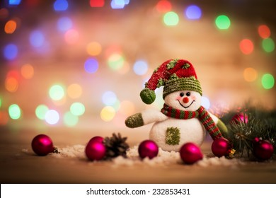 Christmas background with Christmas tree and snowman on a rustic wooden board