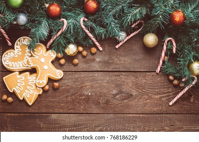 Christmas Background with Christmas Tree, Toys, Gingerbreads, Hazelnuts and Candy Canes on Brown Wooden Background, Free Space for Text, Toned Image