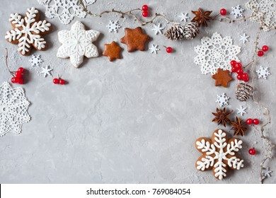 Christmas background with twigs, cones, red berries, lacy snowflakes and gingerbreads