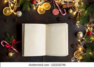 Christmas background with vintage blank open book, decor, lights and fir branches around on dark table, top view. Layout with empty copy space for text.