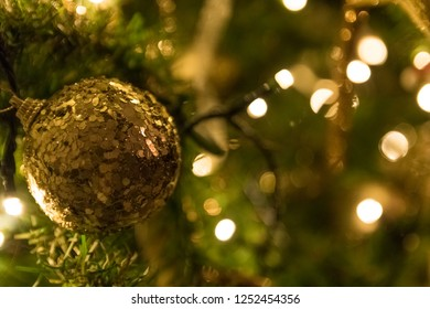 christmas background with Warm white christmas lights and a christmas ball on the right. copy space available.