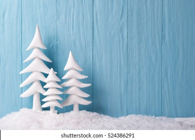 Christmas background with white christmas trees and snow, blue wooden background