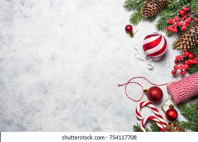 Christmas background or xmas greeting card. Red christmas present box, fir tree branch and decorations. Top view with copy space.