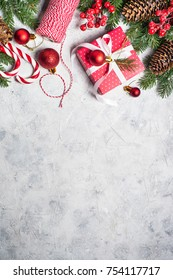 Christmas background or xmas greeting card. Red christmas present box, fir tree branch and decorations on gray stone table. Top view with copy space. Vertical.