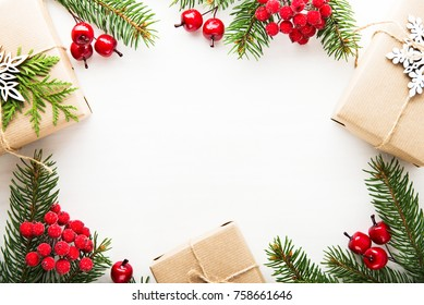Christmas background with xmas tree, gift boxes and red berries on white wooden background. Merry christmas greeting card, frame, banner. Winter holiday theme. Happy New Year. Space for text.