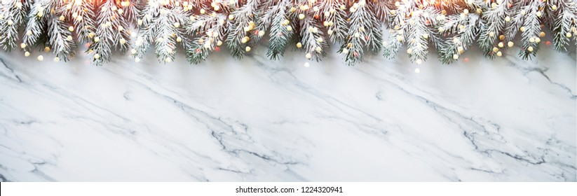 Christmas background with xmas tree on white marble background. Merry Christmas greeting card, frame, banner. Winter holiday theme. Happy New Year. Noel. Space for text. Flat lay
