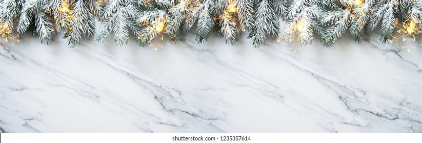 Christmas background with xmas tree on white marble background. Merry christmas greeting card, frame, banner. Winter holiday theme. Happy New Year. Space for text. Flat lay