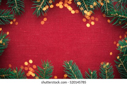 Christmas background with xmas tree and sparkle bokeh lights on red canvas background. Merry christmas card. Winter holiday theme. Happy New Year. Space for text.