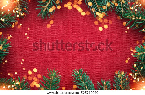 Christmas background with xmas tree and sparkle bokeh lights on red canvas background. Merry christmas card. Winter holiday theme. Happy New Year. Space for text