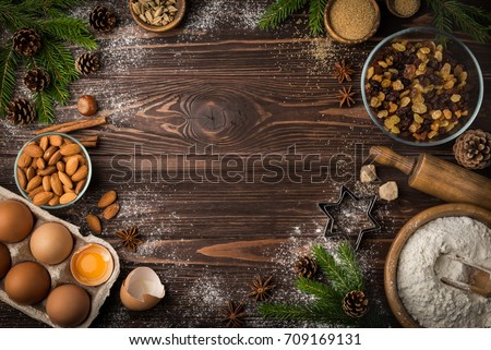 Christmas bakery background. Ingredients for fruit cake ( flour, eggs, butter, nuts, sugar, dried fruits) on wooden table. top view. Copy space