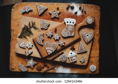 Christmas bakery concept. Delicious gingerbreads and butter cookies lie with cinnamon, cardamon and other seasonings on old wooden boards covered with flour