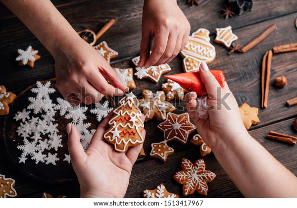 Christmas bakery. Friends decorating freshly baked gingerbread cookies with icing and confectionery mastic. Festive food, family culinary, Christmas and New Year traditions concept