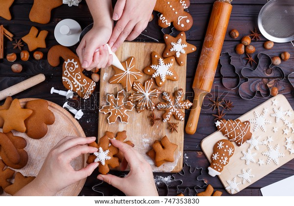 Christmas bakery. Friends decorating freshly baked gingerbread cookies with icing and confectionery mastic, view from above. Festive food, family culinary, Christmas and New Year traditions concept