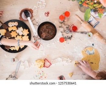 christmas bakery: Girls preparing christmas cookies, top view with sifferent baking supplies, chaotic table