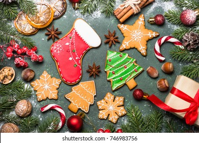 Christmas baking background. Christmas gingerbread cookies with spices and  decorations on green stone table. Top view.