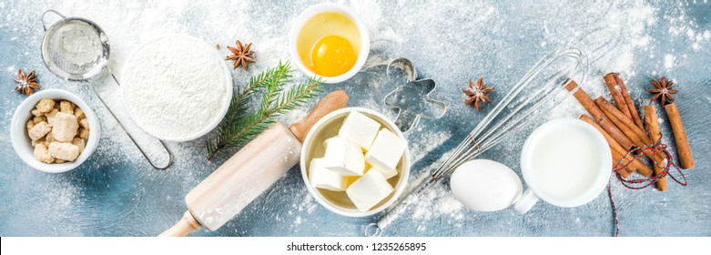 Christmas baking background. Kitchen utensils and ingredients for cooking baking - flour, sugar, eggs, butter, milk, cinnamon sticks, whisk, rolling pin, anise, Blue concrete background banner