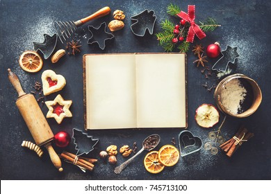 Christmas baking sweet food frame with recipes book, homemade cookies, spices, kitchen utensils, fir branches and red holiday decoration on dark rustic baking tray. Top view