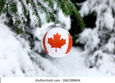Christmas ball with the Canadian symbol on the flag, decorates the snow tree.