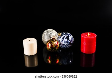 Christmas ball and candles isolated on black background