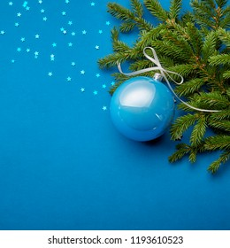 Christmas ball decoration on blue background with fur tree branches and stars