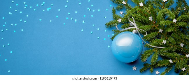 Christmas ball decoration on light blue background with fur tree branches and stars