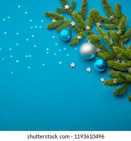 Christmas ball decorations on teal background with fur tree branches and stars