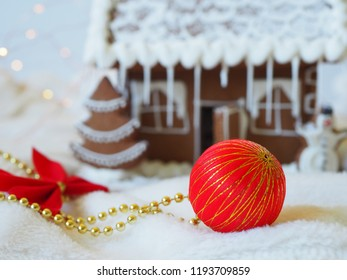 Christmas ball in front of a gingerbread house in the background
