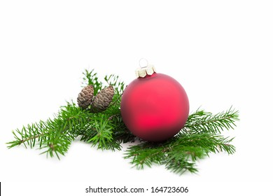 Christmas ball and green spruce branch on white background
