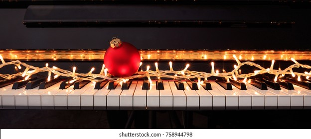 Christmas ball and lights on a classical piano keyboard, front view