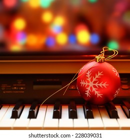 Christmas ball on piano keys. Carol music concept