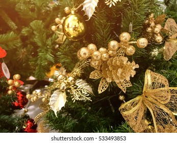 Christmas ball on tree and beautiful gold ribbin and gold ball for New Year holidays and Christmastime celebration for background