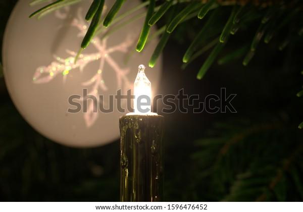 Christmas ball on the Christmas tree in candlelight
