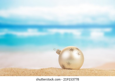 Christmas ball on yellow sand and sea background