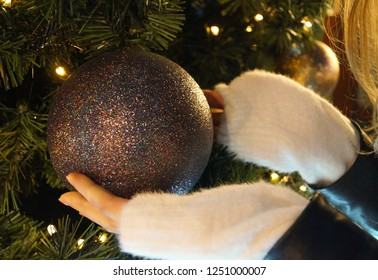 Christmas ball ornament in Christmas tree in hands of a woman with a fluffy snow white sweater