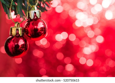 Christmas ball ornaments decoration hanging on fir tree branch over red lights background with copy space