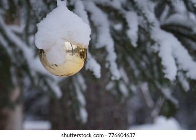 Christmas ball outdoors covered with snow